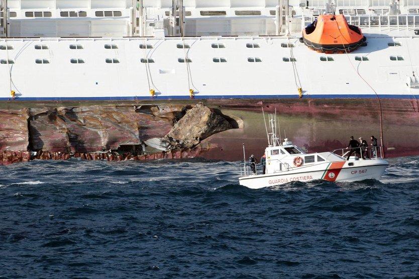 в левом борту Коста Конкордия зияет пробоина в десятки метров и кусок скалы